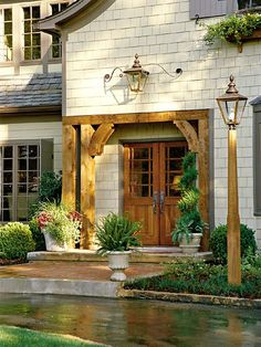 Near this attractive front entry, a series of handsome details--including new double front doors, a spacious landing from the semicircular drive, and classic lighting--welcomes visitors. (Photo: Photo: Jean Allsopp; Stylist: Buffy Hargett)