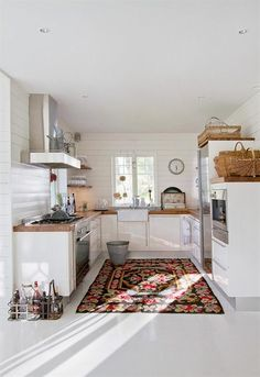 White kitchen, butcher block countertops, farmhouse sink, baskets for extra storage, horizontal plank walls