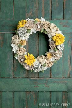 Wrap a straw wreath base with strips of ribbon, then glue a collection of rustic burlap flowers all around—some were readymade and some were DIY'd using a basic ribbon rosette technique.