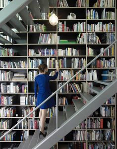 A wireframe staircase leads to a new top floor inside this renovated apartment in Milan by architect Francesco Librizzi. The steel stairs have been fitted close against the shelves to make all the books easily accessible.