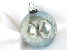 This vintage mod Christmas ornament has a silver glittered stencil in a mod oval and diamond pattern.