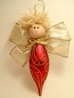 This adorable Angel will make a beautiful addition to your Christmas tree. Her body is a glass teardrop ornament. Her head is a wood ball hand painted. Beautiful gold ribbon for wings.