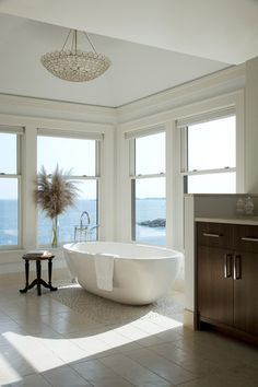 An inviting freestanding tub sits on top of an island stone pebble insert. A custom double vanity made out of zebrawood sits against the far wall.