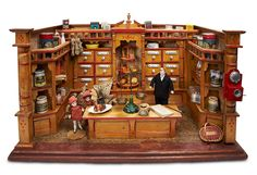 "German grocery store by Christian Hacker, ca. 1890.  23"" l. x 13""h. x 12""d. The natural finish is accented by red trim.  Note the 12  wooden spice drawers with porcelain labels,center niche with display etagere, built-in shelving on the side walls framed by spindled railings, fancy columns at the front,a matching counter and a decorative pediment on the center back. The store is filled with groceries,tins,stoneware jug,bottles,shopping bags,bolts of fabric,and 2 little girls buying sweets."