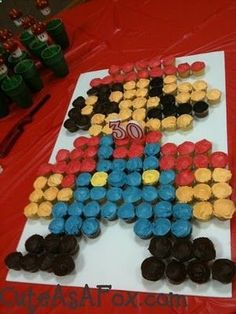 Mario Themed Party - perfect for boys (and for my gamer husband :P): 8-bit Mario Cupcake Cake, Pirahana Plant candy holders, Mario and Luigi Hats for the guests, and Boo Balloons for decor.