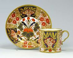 A Spode cup and saucer decorated with an imari design with a fat bird in a reserve, with a flowering plane in the well. Pattern number 1409 in red