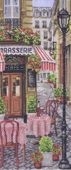 French City Scene A pavement cafe with red and white table covers and the houses in the narrow streets with red geraniums decorating their wrought iron balconies.