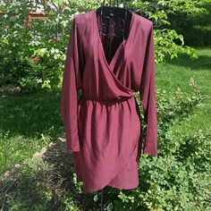 Faux wrap dress size medium This dress is beautiful!  It will never need ironed.  It has an elastic waist and long sleeves.  It measures 32 inches shoulder to hem. The chest size is hard to measure because it has dolman style sleeves.   Size medium. David bitton Dresses