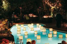 "As the sun went down, floating ""lily pads"" of leaves topped with paper lanterns provided a romantic atmosphere for the backyard wedding reception. Read more: https://www.insideweddings.com/weddings/citrus-themed-summer-wedding-in-california/246/. Photograph by: Michelle Walker Photography"