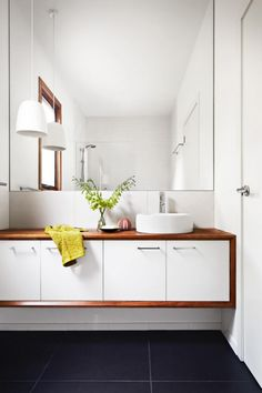 Modern bathroom with grey tiles + white vanity with timber accent | via insideout.com.au #bathroom #timber