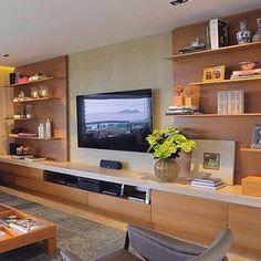 O painel de madeira fica atrás das prateleiras e não da TV, como costuma acontecer nos projetos. Vocês gostam?
