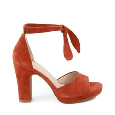 "These wearable low-heeled sandals combine retro femininity with ultimate comfort for wherever life takes you. Featuring a single strap and block heel, they look as darling with skirts as they do cropped pants and jeans. Available in Rust. Heel Height: 4"" Platform: 0.75"" Material: Suede Tie up closure"
