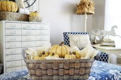 """Decorating for fall doesn't have to take over the entire house and it doesn't have to be traditional """"fall"""" colors. By adding our neutral, white pumpkins inside the natural, rustic baskets, nothing competes with the bold blue in the room. Even our whimsical, animal print pillows add a festive, fall flair without overpowering the space."""