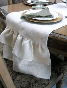 A chic runner made of burlap fabric and ruffles ends. The table runner has no visible seams on the top or sides, joined by 1 seam visible down the center of the bottom of the runner. The 2 ruffles on each end have a double hem along the edges. The ruffle portion on each end is 9 long. Burlap is a delicate fabric with a rustic look, great for country chic decor. Burlap is dry clean only. The color shown is ivory/white burlap. Measurements: up to 108 long by 17 wide (length includes ruffle…