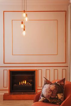 A fireplace in a feminine space. How about those copper borders and naked bulbs.