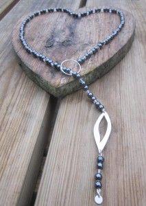 Halssieraad gemaakt van zilver met hematiet en bergkristal.