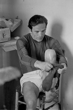 Pier Paolo Pasolini putting on socks