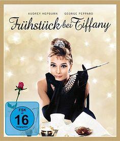 """Frühstück bei Tiffany. Holly (Audrey Hepburn) ist der funkelnde Stern jeder New Yorker Schickeriaparty. Nur manchmal packt sie die Melancholie. Dann tröstet sich Holly mit einem Schaufensterbummel beim Juwelier """"Tiffany's"""". Erst Nachbar Paul ahnt, dass sie hinter ihrer frivolen Fassade tiefe Verletzlichkeit verbirgt…"""