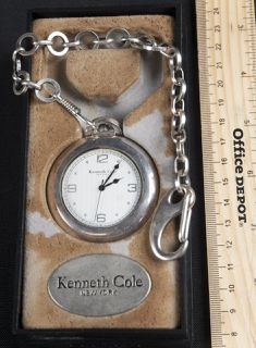 KENNETH COLE POCKET WATCH FOB WITH ORIGINAL BOX. IT HAS A CUSTOM ENGRAVING ON THE BACK. CHAIN MEASURES 9 INCHES IN LENGTH.