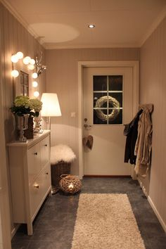 Simple hallway is looking neat and clean. White shoe rack is making area bigger. Mirror on the wall is giving open feeling. Flowers are giving fresh feeling. Lights are making area bright we can see Rectangle shape on the shoe rack.