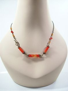 This necklace features beautiful flame red handmade lampwork tube beads, and is accented with Swarovski crystals, and finished with Vintaj natural brass chain and findings.  The necklace is 18 inches