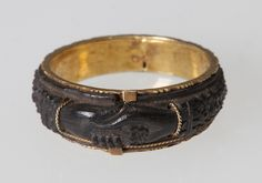 """Mourning ring from the mid-1800s. The clasped hands symbolized """"farewell until we meet again."""" In the 18th & 19th centuries, the use of mourning jewelry was a common form of memorialization. The jewelry was given to family and friends before the procession to the cemetery. The mourning ring was one of the first types of mourning jewelry. The rings would often feature the deceased's name, date of death, and an epithet. Learn more in the Missouri History Museum's blog post: http://bit.ly/1E6g9Hk"""