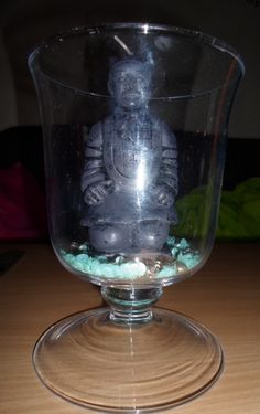 Decoration with turquoise sequins and grey beads mixed in the bottom and a candle on top in a glas.