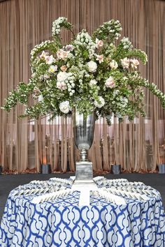 Escort cards sat at a table covered with a blue-and-white patterned tablecloth and a tall silver urn filled with greenery dotted with white blooms, ivory peonies, and light pink roses. #FloralArrangement #TallCenterpiece Photography: KingenSmith. https://www.insideweddings.com/weddings/luxurious-summer-tent-wedding-on-lake-michigan-in-chicago-illinois/671/