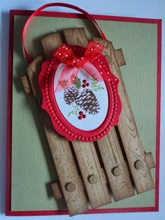 "By Candee Porter. Stamp ""Hardwood"" in brown on kraft cardstock. Trace and cut a round edge near top. Cut into strips. Sponge edges. Use 4 strips for top of sled and two skinnier ones for cross pieces. Punch eight 1/4"" circles from leftovers for nail heads. Assemble sled. Add ribbon ""rope."" Add green mat to red cardstock base. Pop up sled onto card. Add pine cone image. More details on website."