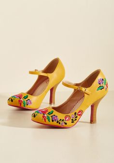 <p>You make exceptional style all your own by rocking these faux-leather pumps from Banned! Glowing with a juicy orange-yellow hue and made all the sweeter with red, purple, and green floral embroidery, these stacked-heel Mary Janes help you surpass all previous ensemble achievements.</p>