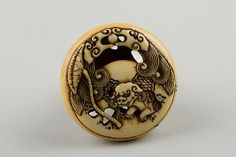 Netsuke Carved with Shishi; reverse with Lotus Leaf  Attributed to Rensai
