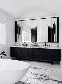This monochrome bathroom features beautiful slabs of New York marble. Bathroom A waterfront house with nature-inspired interiors