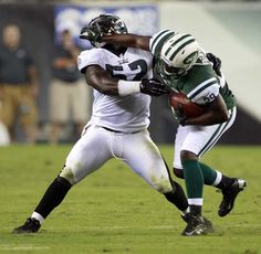 Eagles' Brian Rolle takes a forearm from New York Jets' Bilal Powell during the second quarter in a preseason game on Thursday, August 30, 2012. ( Yong Kim / Staff Photographer )