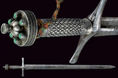 Sudanese Kaskara of the 19th Century   Overall length 110 cm   The sword has a straight, double-edged, European blade, grooved at the centre of the first part and engraved with sun, moon and stars under the effigy of an arm holding a sabre coming out of a cloud. The massive, iron hilt features a cross-shaped quillon, silver grip and pommel richly engraved and decorated with jade and cabochon stones.