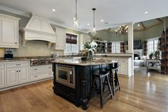 Large white kitchen with dark island, white ceiling, wood floors opening up into the family room