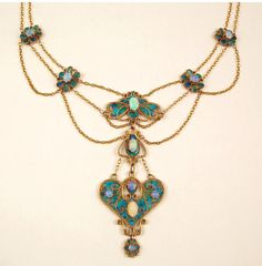 Gold, enamel and opal necklace, Agnes Pool, c1902-1905, the gilded plaques decorated with gold rope twist scrolls and turquoise enamels set with opal cabochons in raised collets united by gold link chains. Agnes Pool was a student of the Birmingham School of Art between 1902 and 1904. Her work was widely exhibited at the Royal Academy, Leeds City Art Gallery and Royal Birmingham Society of Artists. Other Agnes Pool pieces were purchased by the V&A in 1904.