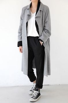 A grey trench-style coat makes for a great addition to any wardrobe. It instantly elevates any look as seen with this casual cool outfit. Throw the classic coat over a black cardigan, a white tee, slouchy black pants, and black high top Converse sneakers. It's that simple!