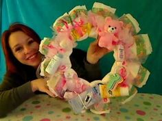 Create this sweet baby shower wreath out of baby diapers! Its simple and fun! Perfect to hang on the front door the day of the shower.   SUPPLY LIST:  •wood or styrafoam wreath craft ring   •string, tulle and ribbon  •12-14 newborn size diapers  •10 or so little baby gift items