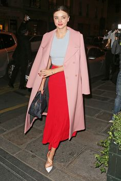 Miranda Kerr does color-blocking correctly in a red pleated maxi skirt, a ribbed crop top, and an elegant pink coat.