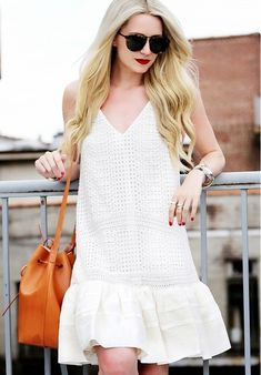 Blair Eadie wears a white eyelet drop waist mini dress, tortoiseshell sunglasses, and a Mansur Gavriel bucket bag