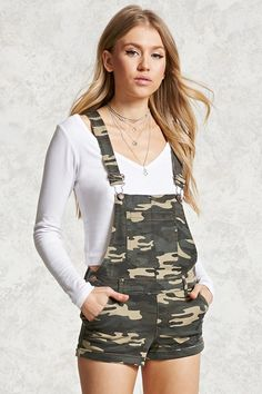 A pair of cuffed denim overall shorts featuring a camo print, bib patch pocket, buttoned sides, five-pocket construction, and adjustable straps.