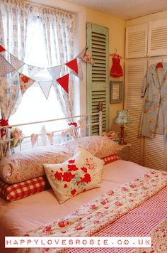 Love the old red and blue vintage reposed bed covers and old shutters on wall very cute