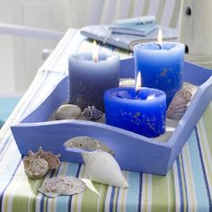 candles in tray with shells and sand