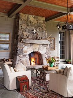 Modern cabin living room with wrought iron chandelier, Persian area rug and dramatic stone fireplace mantel.