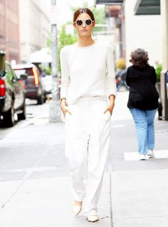 Lily Aldridge wears a white cable knit sweater with white trousers, a white bag and patent flats.