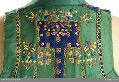 SE Ingelstad. Livkjol med kjol av blåsvart vadmal. 3 våder, den främre slät, bakvåderna goffrerade, helfodrad med blekt fintrådig linnelärft. Sprund mitt fram. Kort liv av halvsiden, blå mönstervävd botten med strödda stiliserade blommor liknande tassavtryck i gult och orange silke. 2 framstycken och 1 ryggstycke. Runt hals, ärmhål, framkanter och över nästan hela ryggen pålagda gröna sidenband 3 cm breda, på och runt banden broderi med silke.