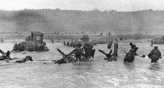 Some of the first assault troops to hit the beachhead in Normandy take cover behind enemy obstacles to fire on German forces as others follow the first tanks plunging through the water towards the German-held shore on June 6, 1944.
