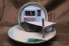 A 1:48 scale miniature beach scene with a beach shop and pier, all set into a teacup and saucer.