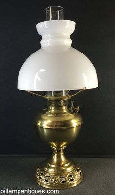 The pattern around the foot of this brass table oil lamp immediately identifies the maker as Bradley and Hubbard (B&H) circa 1900. The pierced pattern around the foot and on the stem just below the font are to allow air to flow through the central draft tube to the inside surface of the circular wick. Air is also drawn to the outside surface of the wick through the mesh around the burner.