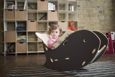 Adorable little girl reading in a Grey Whale Chair by Sprout Kid Furniture